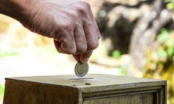 Hand dropping coin in wooden box